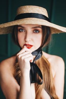 Mulher bonita em um chapéu de palha com fitas pretas.