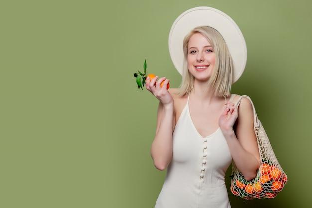 Mulher bonita em um chapéu e vestido branco com um mandarino