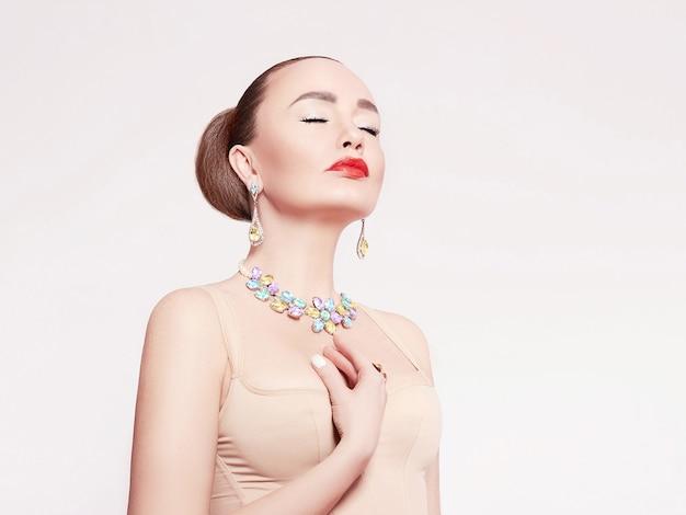 Mulher bonita em um colar, brincos e anel. modelo em joias de pedras preciosas, diamantes.