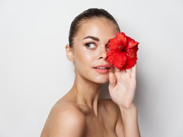 Mulher bonita em um fundo claro com uma flor na mão vista recortada