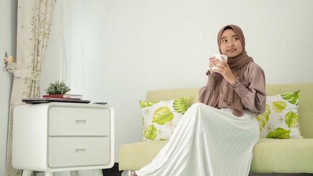 Mulher bonita em um hijab sentada relaxada tomando uma bebida em casa