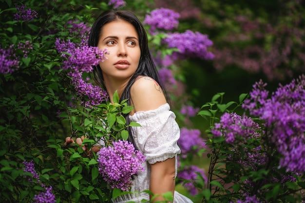 Mulher bonita em um jardim de primavera com lilases florescendo