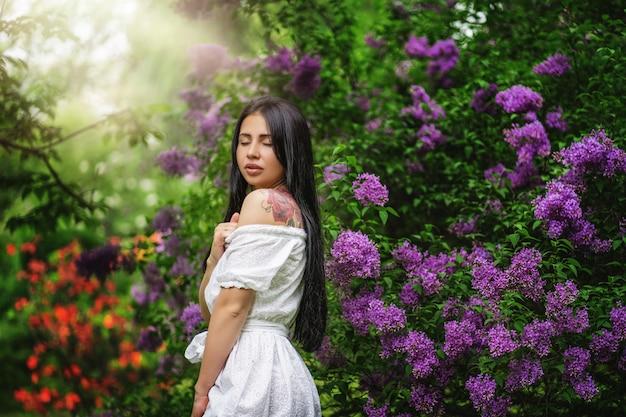 Mulher bonita em um jardim de primavera debaixo de uma árvore florescendo
