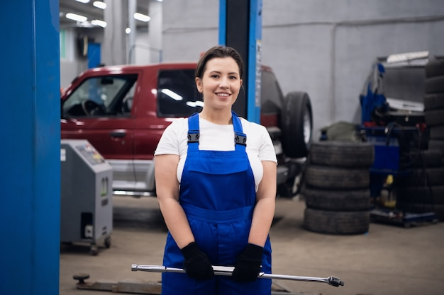 Mulher bonita em um macacão de trabalho segura uma chave inglesa nas mãos e sorri