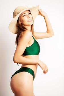 Mulher bonita em um maiô verde posando