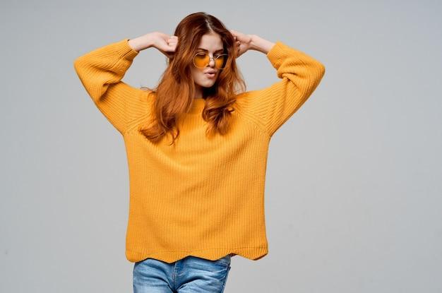 Mulher bonita em um modelo de estúdio de óculos de moda camisola amarela. foto de alta qualidade