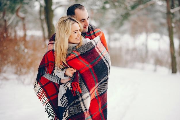 Mulher bonita em um parque de inverno com o marido