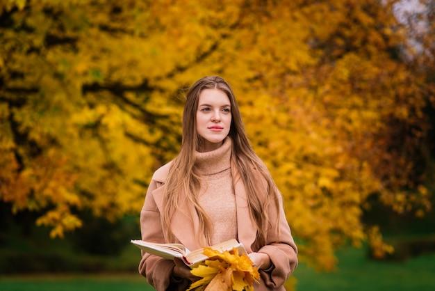 Mulher bonita em um parque durante a temporada de outono