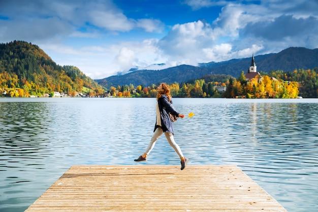Mulher bonita em um píer de madeira no lago bled eslovênia, tempo de outono na europa