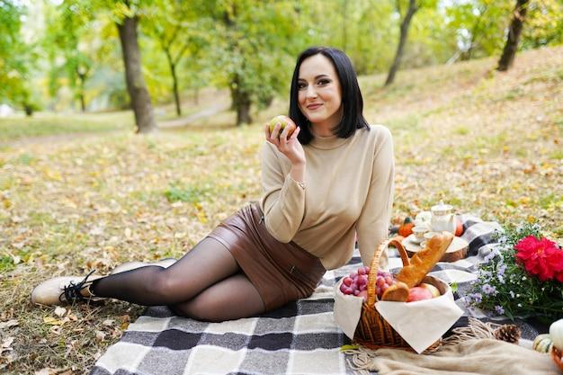 Mulher bonita em um piquenique de outono com flores, folhas de outono e abóbora, feriado de ação de graças