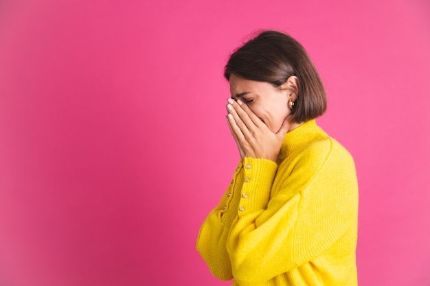 Mulher bonita em um suéter amarelo brilhante isolado em rosa depressão estressante de choro