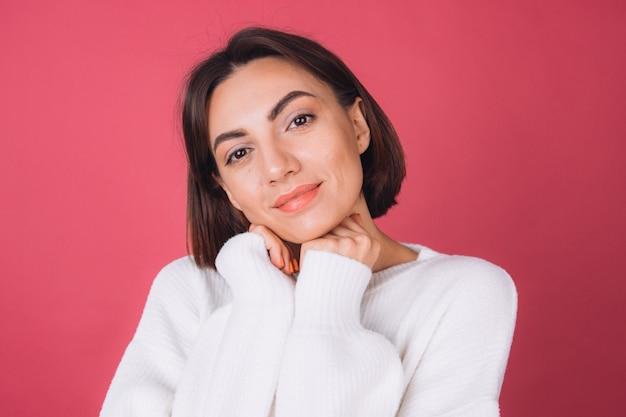 Mulher bonita em um suéter branco casual, isolada em pé, rosto calmo, sorriso fofo, cópia espaço