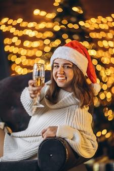 Mulher bonita em um suéter quente, meias e chapéu de natal, sentada na cadeira com champanhe