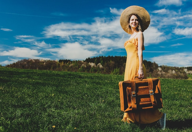 Mulher bonita em um vestido amarelo e uma mala em um prado de montanha com flores