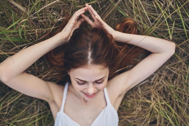 Mulher bonita em um vestido branco ao ar livre deitada na palha
