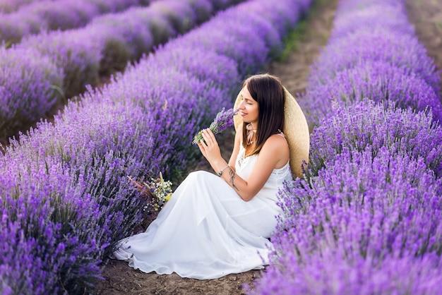 Mulher bonita em um vestido branco e um chapéu coleta lavanda. fotos de verão.