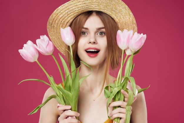 Mulher bonita em um vestido com buquê de flores fundo rosa