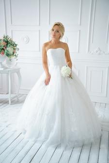 Mulher bonita em um vestido de noiva com uma bela maquiagem e cabelo