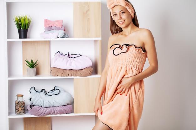 Mulher bonita em um vestido de toalha com pele perfeita após tratamentos de spa em casa