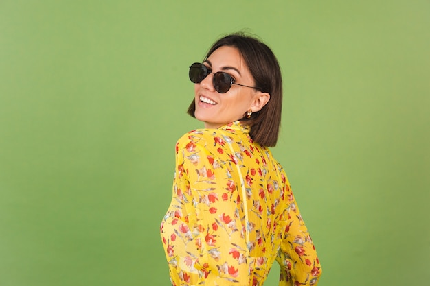 Mulher bonita em um vestido de verão amarelo e óculos escuros, estúdio verde, feliz, alegre, alegre, emoções alegres