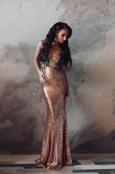 Mulher bonita em um vestido longo dourado olhando de lado