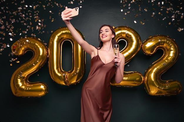 Mulher bonita em um vestido moderno de luxo, fazendo selfie com champanhe na frente de balões dourados isol ...