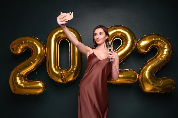 Mulher bonita em um vestido moderno de luxo, fazendo selfie com champanhe na frente de balões dourados isol ... Foto Premium
