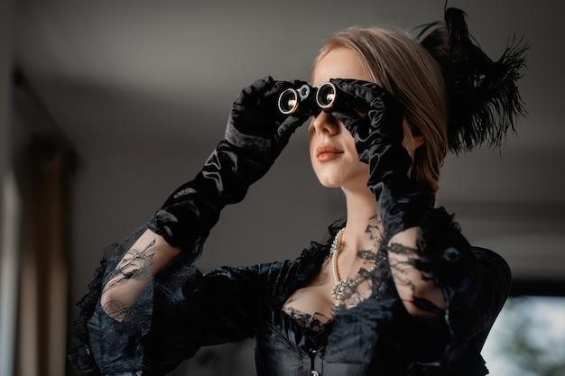 Mulher bonita em um vestido preto vintage segurando uma ópera no interior