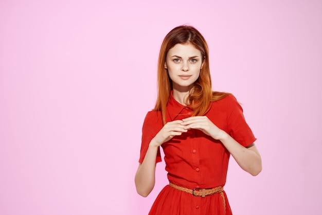 Mulher bonita em um vestido vermelho com gestos com as mãos fundo rosa