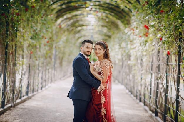 Mulher bonita em um vestido vermelho longo anda pela cidade com o marido