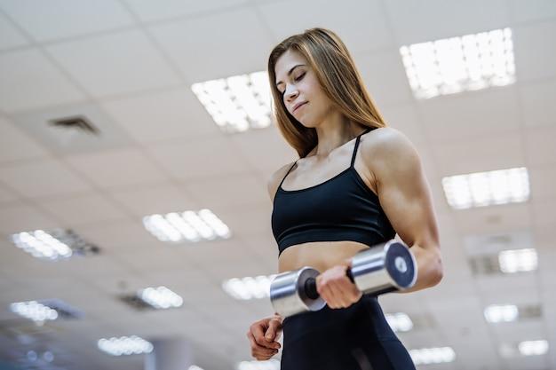 Mulher bonita em uma barra de retenção desgaste desportivo em uma mão no ginásio.