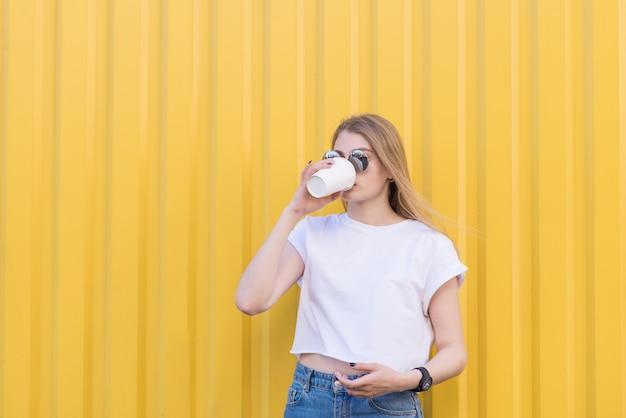 Mulher bonita em uma camisa branca, bebendo café em copos de papel em uma parede amarela.