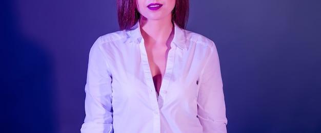 Mulher bonita em uma camisa branca com luzes de estúdio
