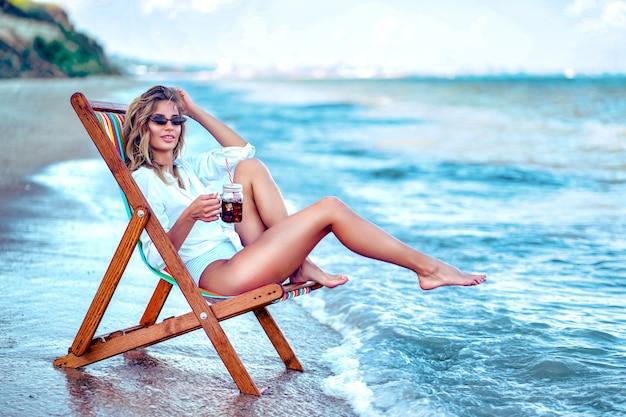 Mulher bonita em uma camisa branca relaxando em uma espreguiçadeira na praia e tomando uma bebida na praia