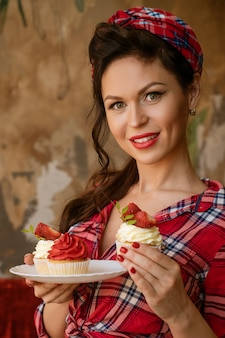 Mulher bonita em uma camisa com maquiagem segurando um bolinho de morango