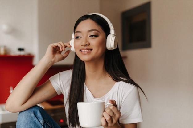 Mulher bonita em uma camiseta branca e fones de ouvido está ouvindo música enquanto toma uma xícara de chá
