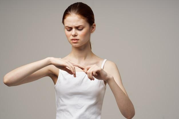 Mulher bonita em uma camiseta branca gesticulando com as mãos na luz de fundo vista recortada