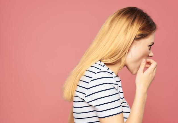 Mulher bonita em uma camiseta listrada descontente perturbou as emoções do estúdio