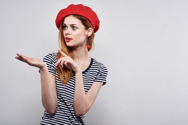 Mulher bonita em uma camiseta listrada gesto de lábios vermelhos com as mãos em um fundo claro