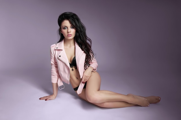 Mulher bonita em uma jaqueta de couro rosa com cabelos longos no chão. menina morena sexy