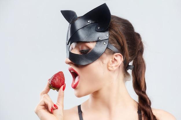 Mulher bonita em uma máscara de gato. sedutoramente posando com morangos