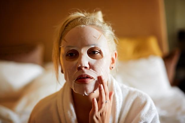 Mulher bonita em uma máscara facial, pele limpa, aparência saudável