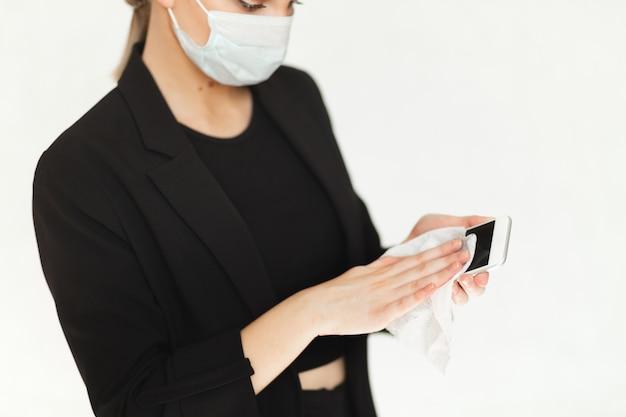 Mulher bonita em uma máscara protetora de vírus médico limpa seu telefone com toalhetes antibacterianos