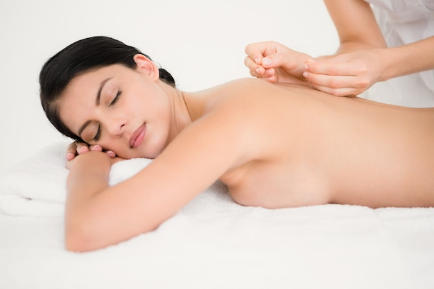Mulher bonita em uma terapia de acupuntura no spa de saúde