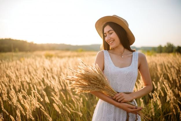 Mulher bonita em vestido branco e chapéu de palha colhe trigo no campo. menina bonita no prado do verão