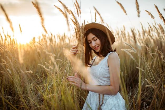 Mulher bonita em vestido branco e chapéu de palha mantém buquê de trigo no campo. menina bonita no prado do verão