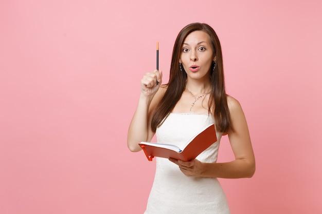 Mulher bonita em vestido branco tem uma ideia nova, escrevendo notas no diário, caderno