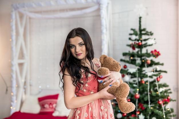 Mulher bonita em vestido de noite posando com ursinho de pelúcia