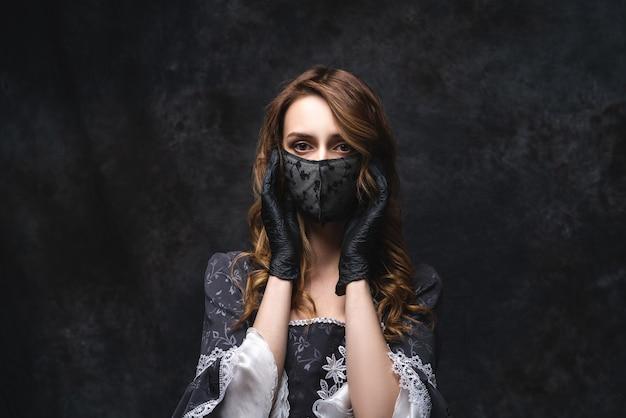 Mulher bonita em vestido renascentista, máscara facial e luvas, coronavírus, conceito de proteção covid-19.