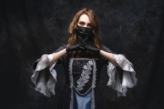 Mulher bonita em vestido renascentista, máscara facial e luvas, coronavírus, conceito de proteção covid-19. Foto Premium